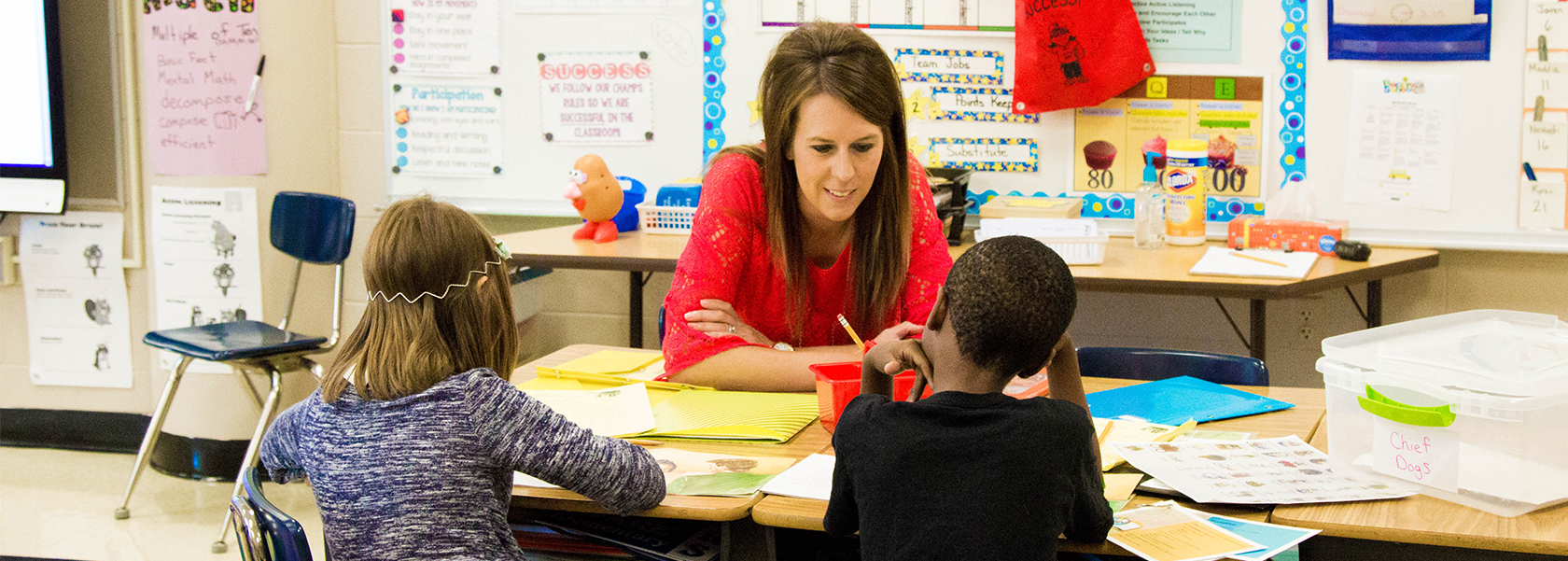 Photo of principal Alicia Scofield working with students in a classroom.